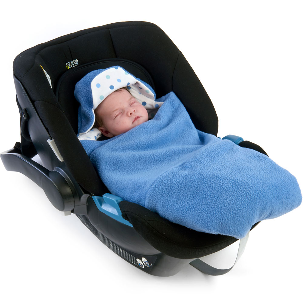 a baby wrapped in a morrck china blue and spot car seat blanket in a car seat