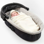 a baby wrapped in a morrck cream car seat blanket in a carry cot