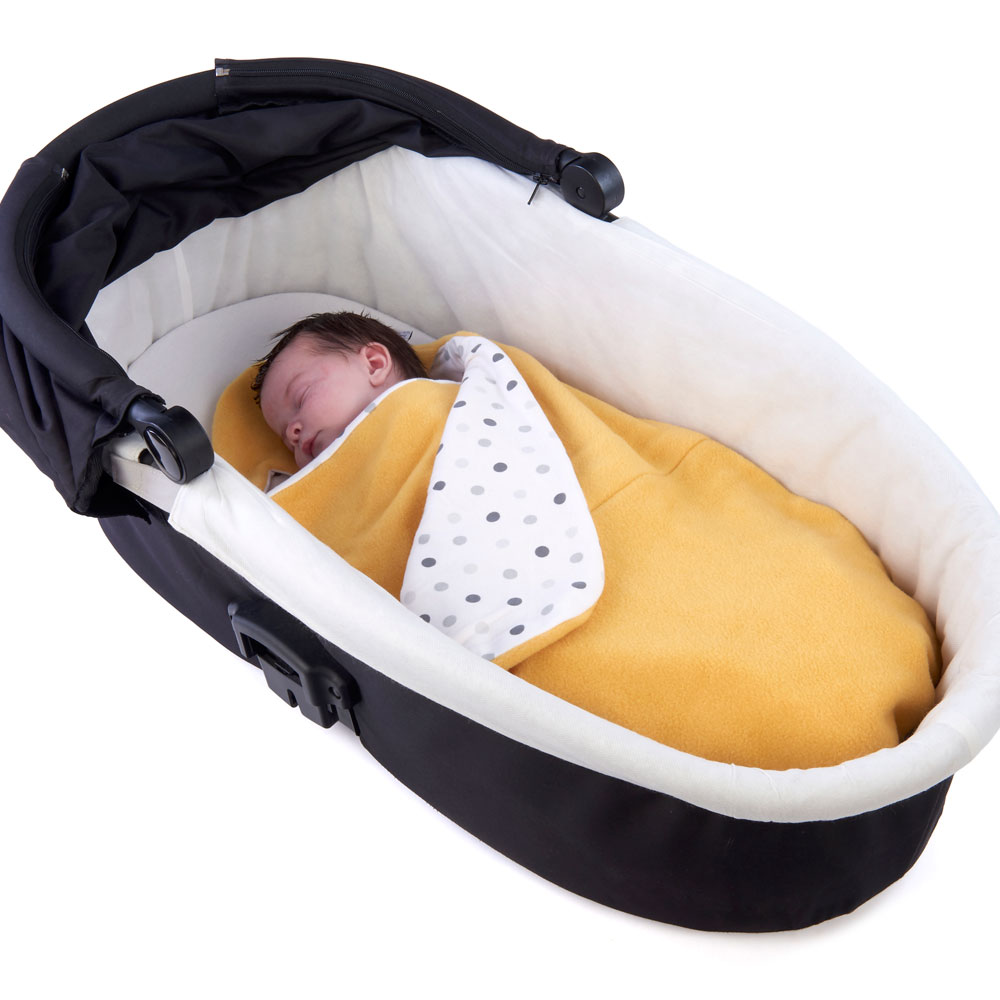 a baby wrapped in a morrck custard and spot car seat blanket in a carry cot
