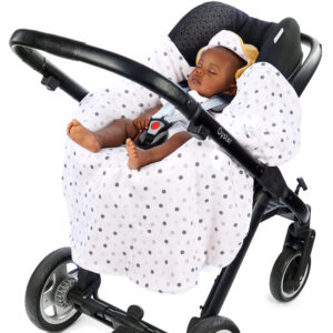 a baby in a morrck custard and spot car seat blanket unwrapped in a travel system