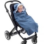 a toddler wrapped in a morrck denim grey and spot car seat blanket in a buggy