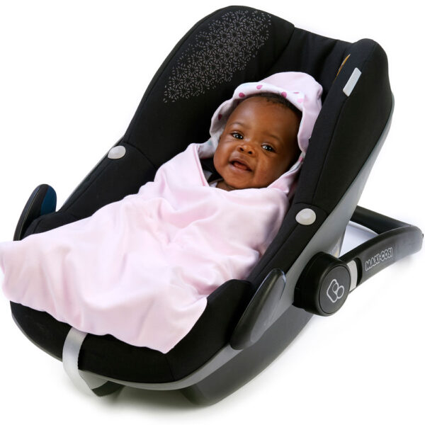 a baby wrapped in a morrck pastel pink and spot lightweight car seat blanket in a car seat