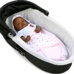 a baby wrapped in a morrck pastel pink and spot lightweight car seat blanket in a carry cot