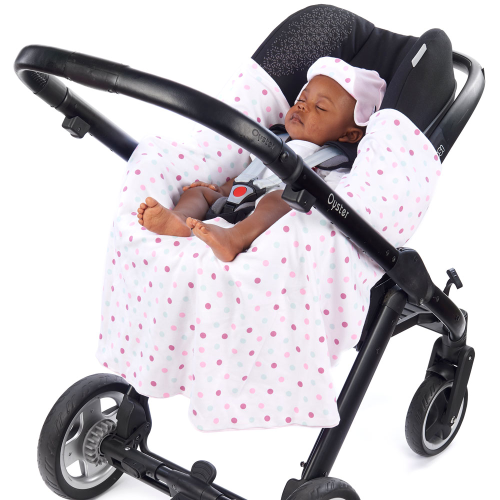 a baby in a morrck pastel pink and spot lightweight car seat blanket unwrapped in a travel system