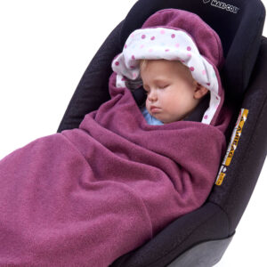 a toddler wrapped in a morrck plum and spot car seat blanket in a car seat
