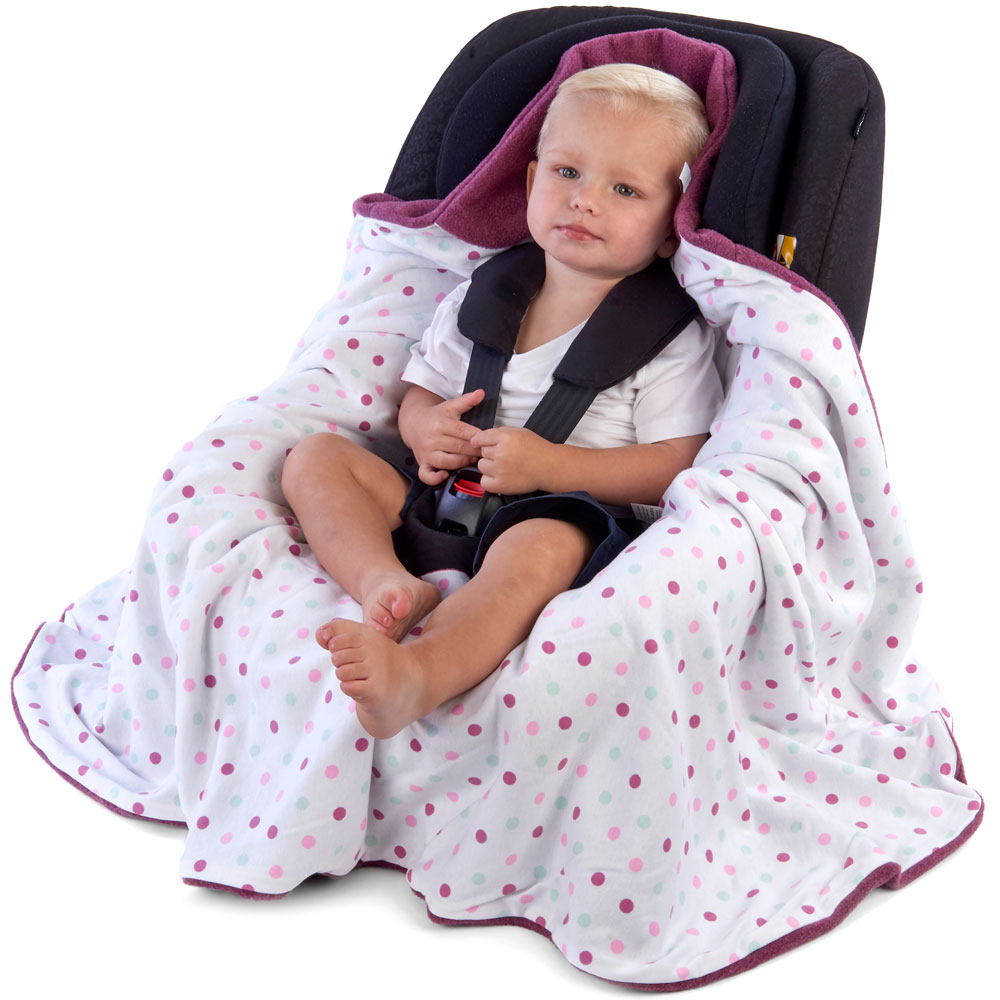 a toddler in a morrck plum and spot car seat blanket unwrapped in a car seat
