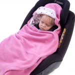 a toddler wrapped in a morrck sherbert pink and spot car seat blanket in a car seat