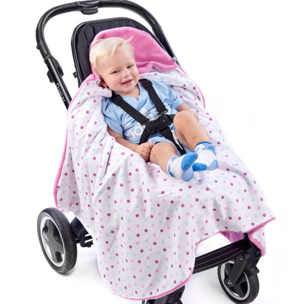 a toddler in a morrck sherbert pink and spot car seat blanket unwrapped in a buggy