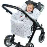 a baby in a morrck silver grey and spot car seat blanket unwrapped in a travel system