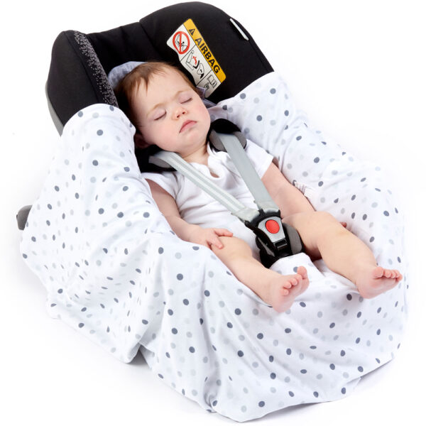 a baby in a morrck grey marl and spot lightweight car seat blanket unwrapped in a car seat