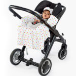 a baby in a morrck white and spot lightweight car seat blanket unwrapped in a travel system